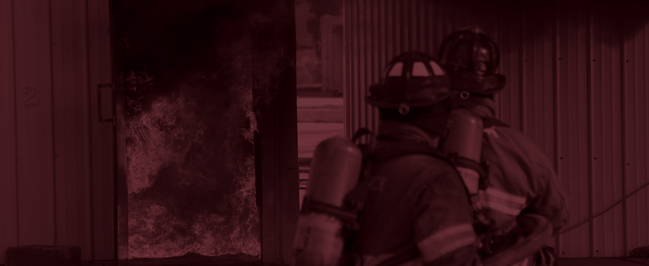 Fire fighters approaching a fire in a building with hose