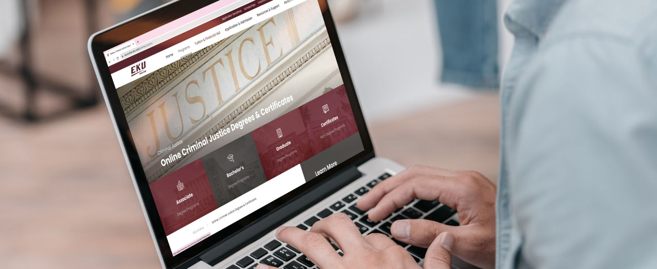 Man looking at EKU's Online criminal justice program on a laptop