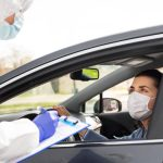 Health worker in mask writes down details of person in car before administering a vaccine