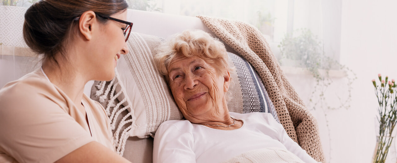 Social Worker smiling and talking with elderly client