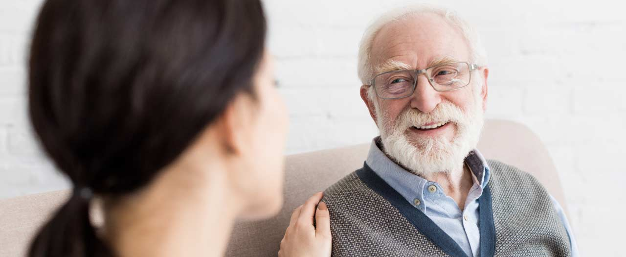 Social worker smiling as she speaks with elderly patient