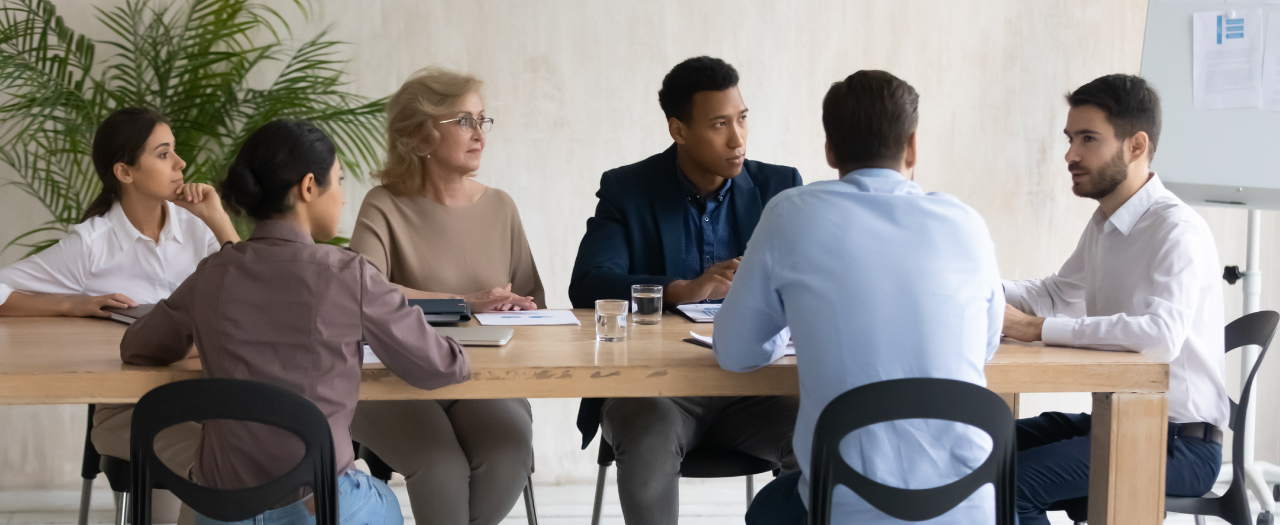 Coworkers of a variety of ages discuss at a table