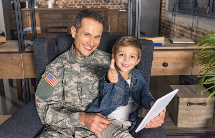 Smiling veteran at home with his son