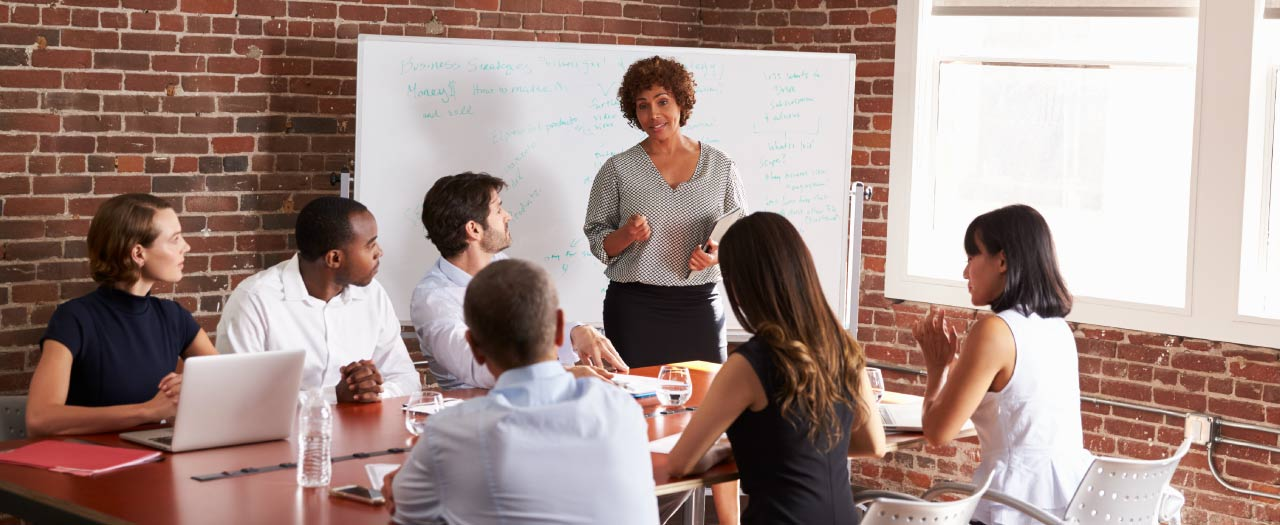 MBA graduate speaks with confidence at a business meeting