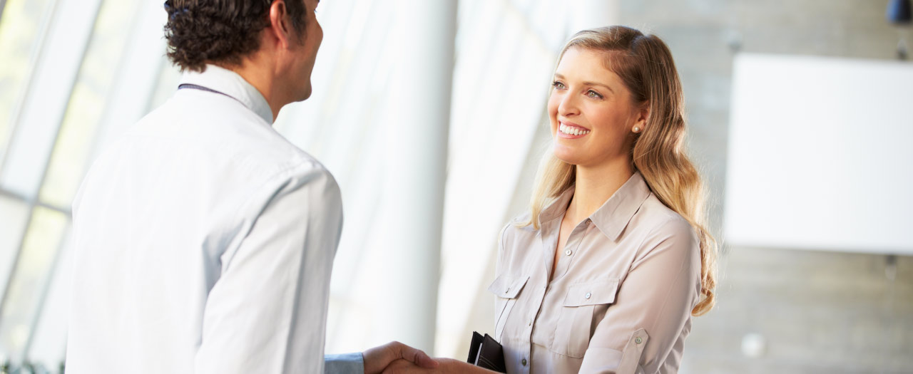 Instructional Designer shaking hands with new coworker at professional association