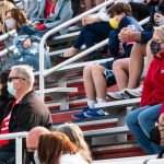 Football fans wear masks as they sit apart in the stands