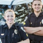 Two police officers smiling next to cruiser