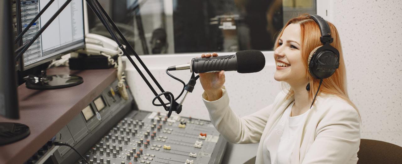 Smiling radio host working in sound room